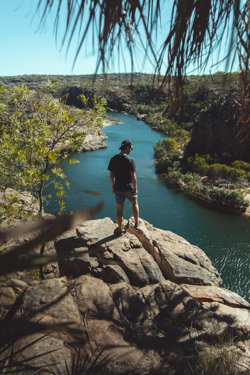 man standing on a cliff overlooking land and river